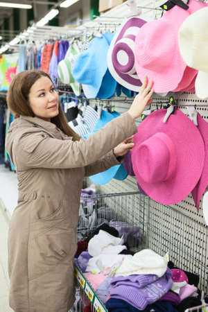 Woman looking for summer hats on shop shelf photo