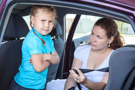 Child refusing to seat into infant car safety seat photo