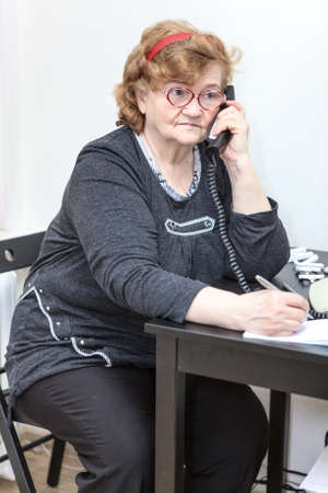 Elder Caucasian woman at workplace with phone in office photo