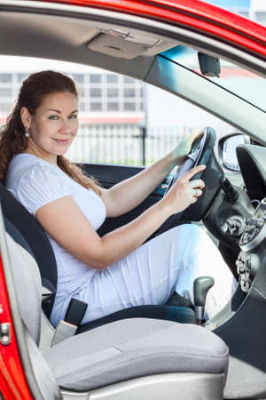 Attractive woman through the opened door sitting in red car photo
