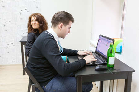 freelancers: Young man typing with laptop and cheerful girlfriend sitting near Stock Photo