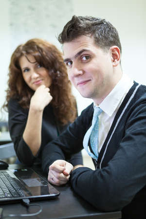 freelancers: Smiling young couple with laptop looking at camera together Stock Photo