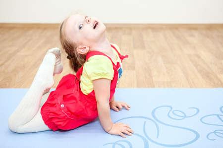 Flexible child making gymnastics on floor photo