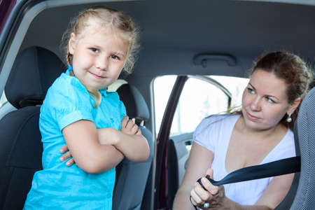resentful: Resentful child ignoring mother forcing to seat into infant car safety seat Stock Photo