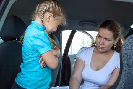 resentful: Resentful child refusing get in safety car seat under mother severe look