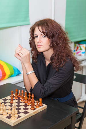 game room: Thoughtful girl sitting at the board with chess