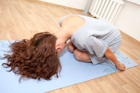 stretched: Young woman doing an aerobic exercises sitting on mat