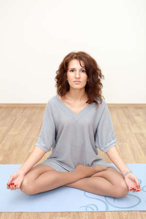 Beautiful Caucasian woman practicing yoga on floor in gym photo