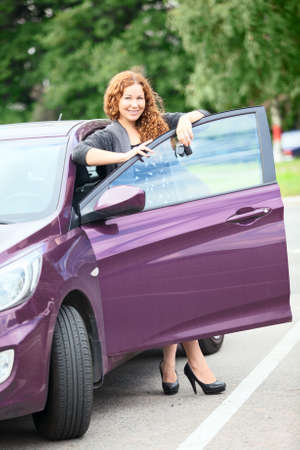 Attractive woman with keys standing near own car photo