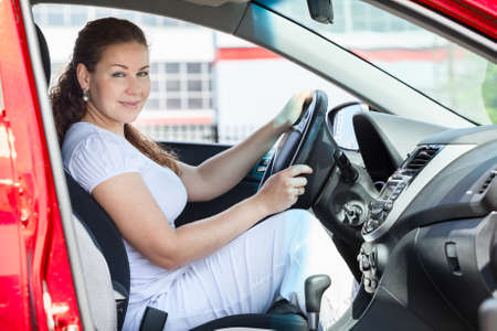 Attractive woman holding car wheel through the opened door photo
