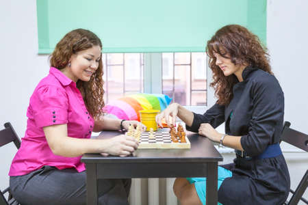 game room: Two young women playing chess