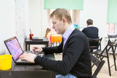freelancers: Young man sitting in room, typing on laptop computer
