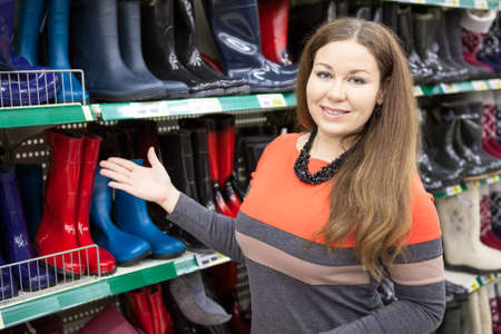 merchandiser: Woman salesman standing near store shelves and showing waterboots Stock Photo