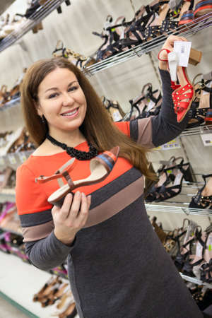 Attractive woman buying shoes in the shopping center photo
