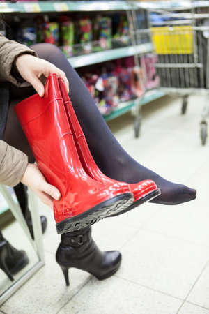 Customer trying red rubber boots in shop hall Stock Photo