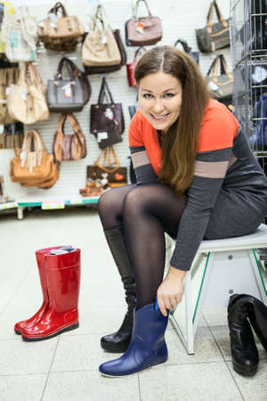 rubber sole: Attractive young woman trying blue waterboots in hand Stock Photo