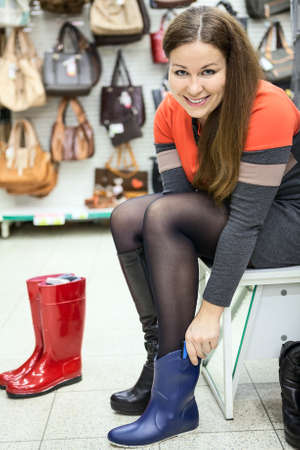 Happy smiling woman wearing rubber boots in the shop