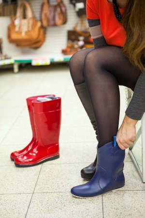 Unrecognizable young woman trying blue waterboots in hand photo