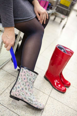 Unrecognizable woman trying new waterboots in the shop photo
