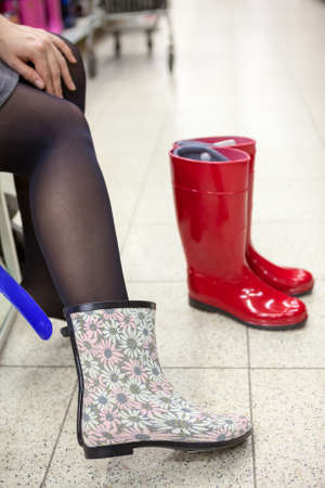 rubber sole: Dressing and buying rainboots in shoeshop Stock Photo