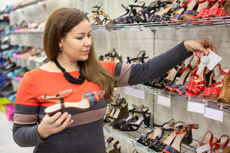 Beautiful Caucasian woman choosing shoes in the shopping center photo