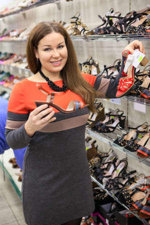 Attractive smiling woman choosing shoes in the shopping center photo