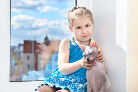 pvc: Young girl sitting with cat on window sill Stock Photo