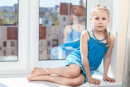 Young child sitting on white window sill in sun light photo