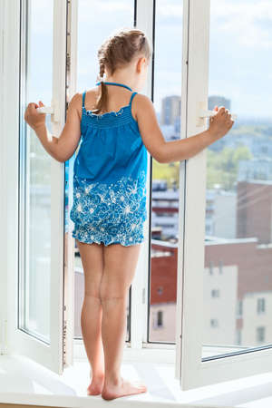 teenage problems: Girl teenager standing on window with opened door, looking down from height