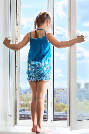 Young girl standing on window with opened door, looking from height photo