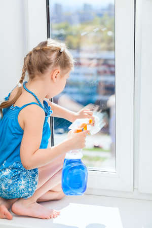 Washing windows with a rag and spray, small girl in blue dress photo