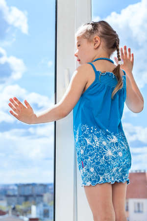 looking through window: Small child looking through window, standing on windowsill