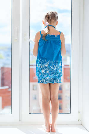 double glazing: Rear view of full length pretty girl behind window glass