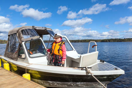 jung: Jung a child in captains cap standing on wooden pier in moored motor boat Stock Photo