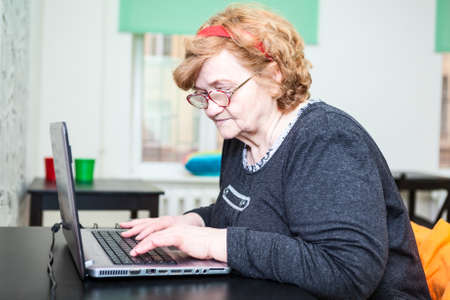 Elder woman looking close and typing on laptop keyboard