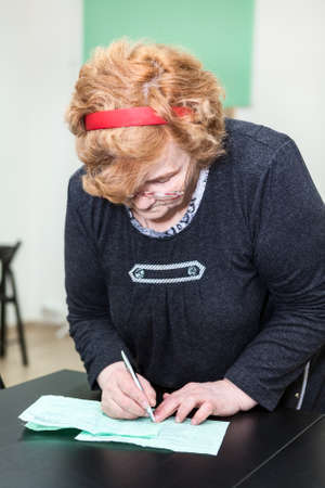 Senior age Caucasian woman writing forms at table photo