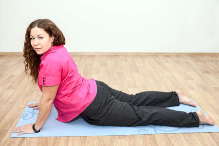 Girl lying on the mat in one of the yoga positions photo