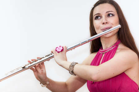 silver flute: Close up portrait of young woman playing on flute, white background Stock Photo