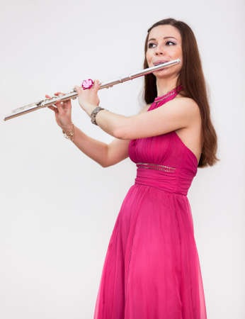 Attractive Caucasian woman a flutist playing on silver flute, white background