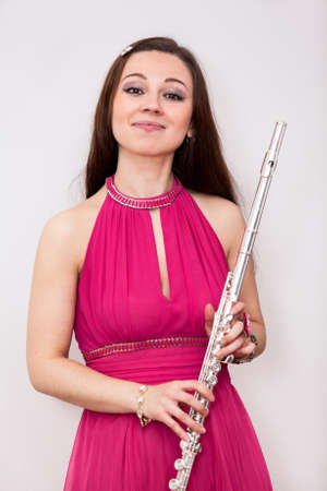 silver flute: Woman fluist with a silver flute looking at camera Stock Photo