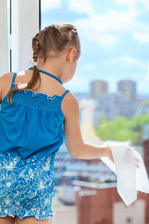 Little girl rubbing glass with cloth on plastic window photo
