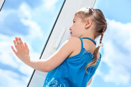 Side view of pretty girl behind plastic window glass Standard-Bild