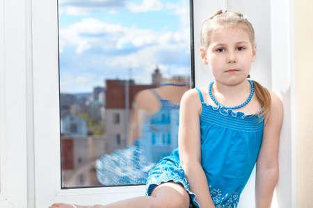 double glazing: Calm pretty girl in blue dress sitting on window sill