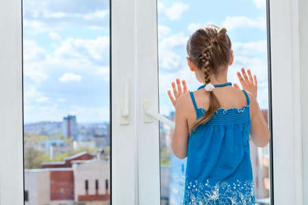 Little child looking through the window glass, copyspace, rear view photo