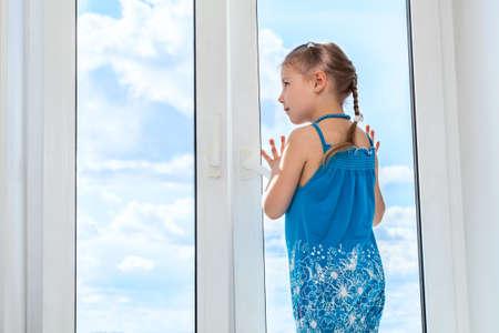 Meisje op zoek naar de blauwe hemel door het raam, copyspace