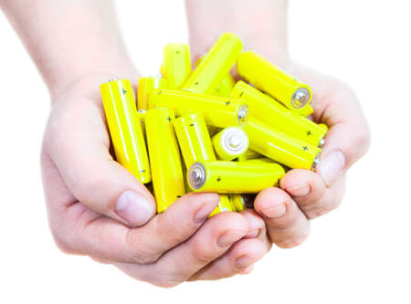 Caucasian handful with lot yellow penlight batteries isolated on white background photo