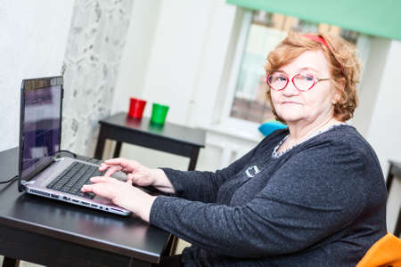 Retirement age woman sitting at table with laptop on table, looking at camera photo