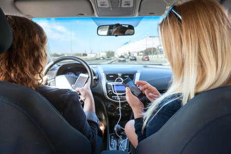 aandrijvingen: Twee vrouwen met mobiele telefoons in hun handen het rijden in de auto Stockfoto