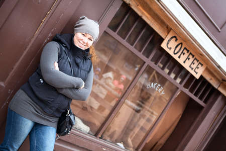Smiling happy Caucasian woman standing on old city street photo
