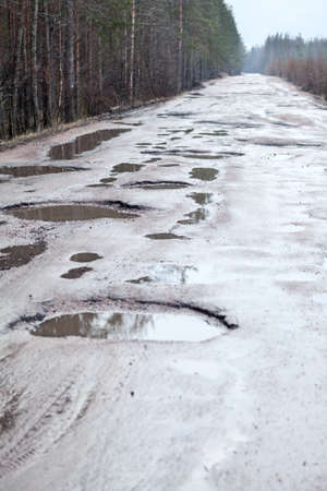 Holes and puddles on bad broken road in woods photo